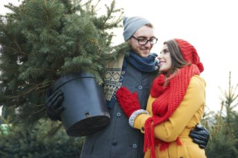 A man and a women with a real Christmas tree