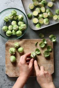 Hands cutting brussels sprouts on a chopping board