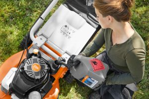 Moto4Plus being poured into STIHL petrol lawn mower