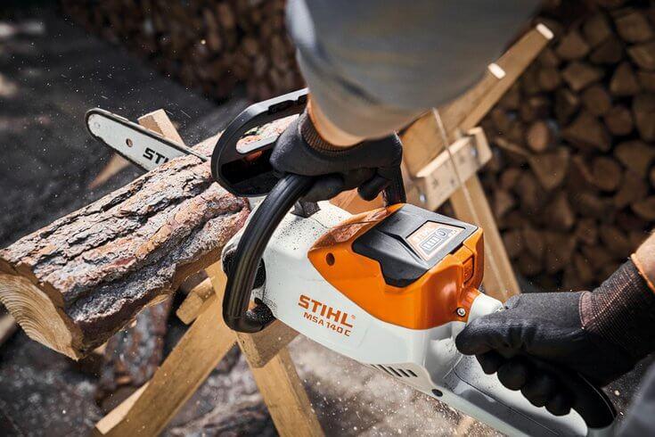 STIHL MS 140 CB cordless chainsaw cutting through a log