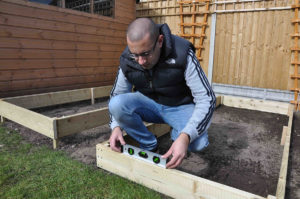 check the raised bed is level using a spirit level